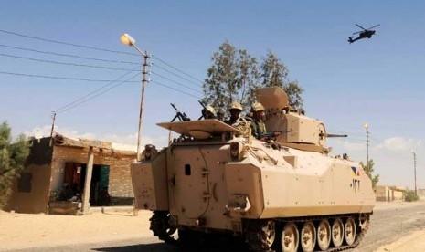 Tentara Mesir berpatroli di sebuah kendaraan lapis baja yang didukung oleh helikopter tempur di Sheikh Zuweyid, Sinai Utara, Mesir, Selasa (21/5).