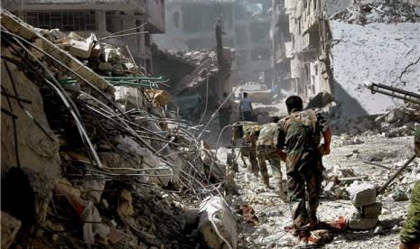 Tentara Suriah berjalan di antara bangunan yang hancur akibat perang saudara yang melanda negara tersebut.