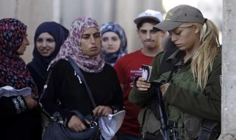 Tentara wanita zionis Israel memeriksa kartu identitas warga Palestina ...