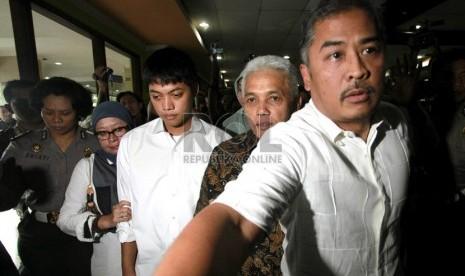 Tersangka kasus kecelakaan di Tol Jagorawi, Rasyid Rajasa (Tengah) didampingi orangtuanya Hatta Rajasa dan Okke Rajasa, tiba di Ditlantas Polda Metro Jaya untuk menjalani pemeriksaan, Jakarta, Senin (7/1). (Republika/Adhi Wicaksono)