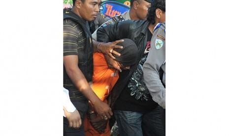 Tersangka kasus pembunuhan Angeline, Agus (tengah) digiring polisi saat mengikuti rekonstruksi di rumah majikannya, Margriet Megawe di Denpasar, Senin (6/7).  (Antara/Nyoman Budhiana)