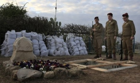 Tiga tentara berdiri di pinggir makam Ariel Sharon dalam prosesi penguburan mantan perdana menteri Israel itu di samping makam Istrinya, di Gunung Negev, dekat perbatasan Gaza pada Senin (13/1/2014)