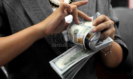 Transaksi penukaran Rupiah terhadap mata uang asing di salah satu tempat penukaran uang, Jakarta, Kamis (23/7).
