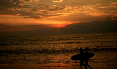 Two surferers pass during a sunset at Kuta beach, Bali. (illustration)