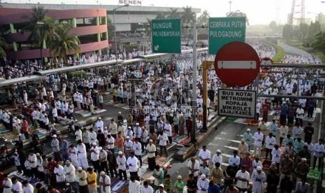 Umat Muslim tengah mengikuti Shalat Idul Fitri di pelataran jalan