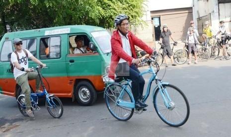 Wali Kota Bandung, Ridwan Kamil menggunakan sepeda menuju Terminal Dago untuk mengemudikan kendaraan angkot dalam acara 'Angkot Day' Jumat (20/9).   (Republika/Edi Yusuf)