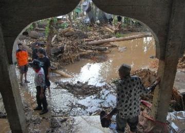 Warga berjalan di kawasan yang terkena banjir bandang, di Jorong Sawah Laweh, Nagari Simpang, Kecamatan Simpati, Kabupaten Pasaman, Sumbar, Kamis (23/2).