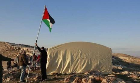 Warga memasang bendera Palestina dekat kota Jerusalem.