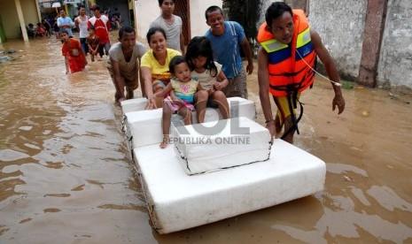 Warga menyelamatkan keluarga mereka saat banjir merendam rumah mereka di Kampung Poncol,Kelurahan Bukit Duri, Kecamatan Tebet,Jakarta Selatan,Senin (24/12).  (Republika/Prayogi)