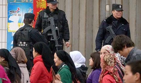 Warga Muslim Uighur berjalan melintas di depan tentara yang berjaga di kawasan Xinjiang Cina.