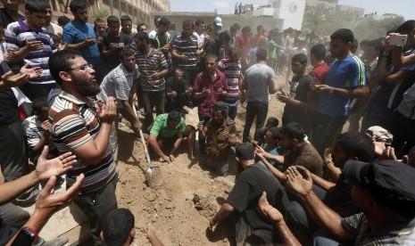 Warga Palestina berdoa usai pemakaman korban serangan Israel
