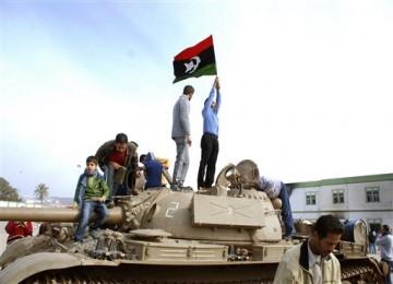 Warga mengibarkan bendera Libya sebelum era Gaddafi di dalam markas militer di Benghazi, Senin (21/1).