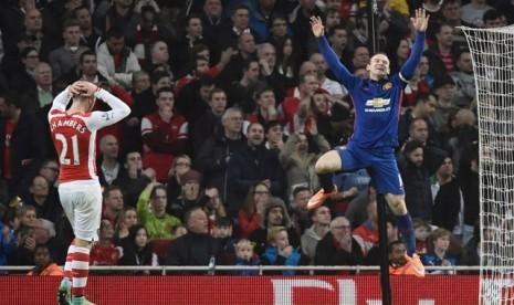 Wayne Rooney melompat kegirangan seusai mencetak gol ke gawang Arsenal, Ahad (23/11) dini hari WIB.