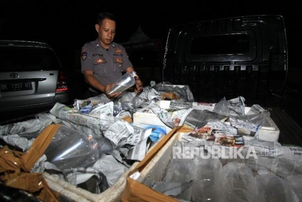 [ilustrasi] Seorang polisi dengan barang bukti benih lobster atau benur.