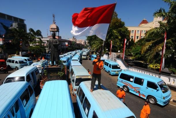 [ilustrasi] Seorang sopir angkutan umum mengibarkan bendera Merah Putih saat aksi unjuk rasa menolak transportasi berbasis daring atau