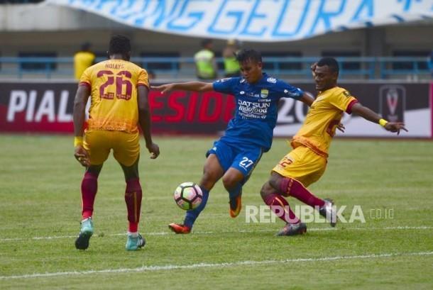 Pemain Persib Bandung Puja Abdilah dan diadang dua pemain Sriwijaya FC pada laga perdana Piala Presiden antara Persib Bandung melawan Sriwijaya FC di Stadion Gelora Bandung Lautan Api, Bandung, Selasa (16/1).