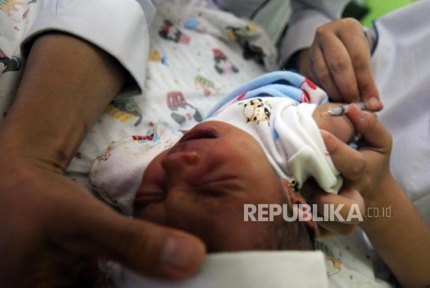 Balita menangis saat disuntik imunisasi difteri di Puskemas Cimanggis, Depok, Jawa Barat, Rabu (6/12).