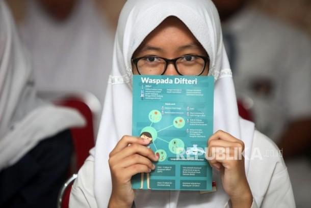 Seorang siswi memperlihatkan brosur waspada difteri. Ilustrasi