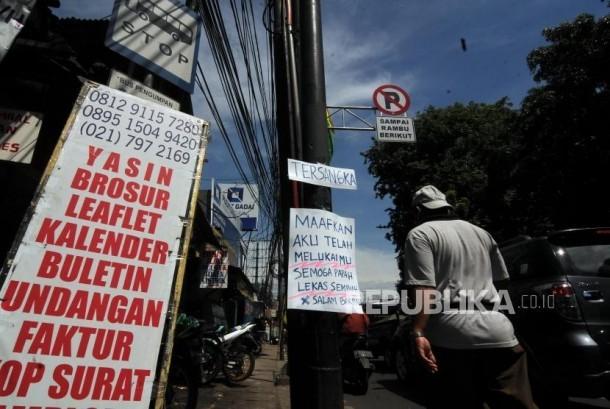 Sebuah tiang listrik dipasangkan poster bertuliskan kalimat sindiran untuk Ketua DPR Setya Novanto di Jalan Raya Pasar Minggu, Jakarta Selatan, Senin (20/11).
