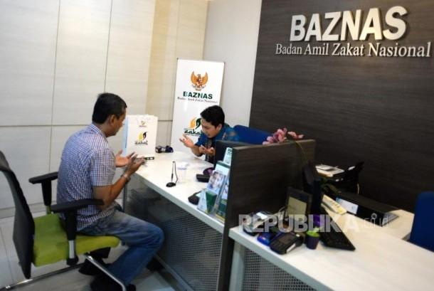 Target Penghimpunan Zakat Baznas. Muzaki membayarkan zakat dengan petugas di kantor palayanan Baznas, Jakarta, Kamis (2/11).