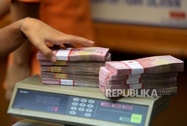 Petugas menghitung mata uang rupiah. (ilustrasi)