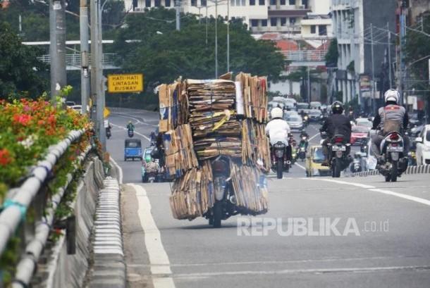 Sebuah sepeda motor dengan bermuatan tumpukan kardus bekas melintas di kisaran fly over Senen Jakarta, Selasa (4/7). Membawa barang dengan kapasitas berlebih pada sepeda motor dapat membahayakan dipengendara dan pengguna jalan lainnya. Foto: darmawan.