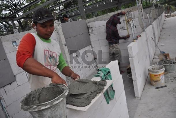 Pekerja mengerjakan pembangunan kios di Lapangan eks IRTI Monas, Jakarta Pusat, Kamis (21/8).   (Republika/Rakhmawaty La'lang)