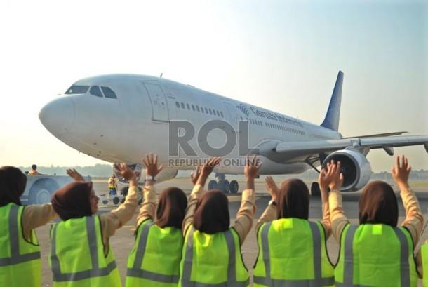 Petugas melambaikan tangan ke pesawat yang mengangkut calon jamaah haji kloter pertama embarkasi Solo di Bandara Adi Soemarmo, Solo, Senin (1/9). (Republika/Edwin Dwi Putranto)