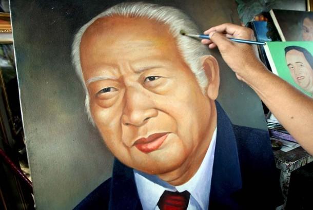 Seroang pelukis melukis wajah presiden kedua RI Soeharto.