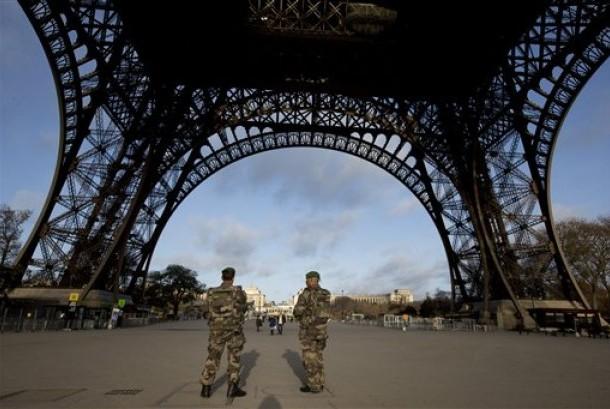 Tentara Prancis berpatroli di Menara Eiffel yang ditutup pada hari pertama berkabung nasional di Paris, Ahad (15/11).  (AP/Peter Dejong)