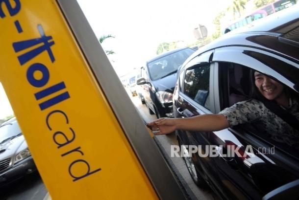 Pengendara menggunakan e toll card saat masuk gerbang tol.