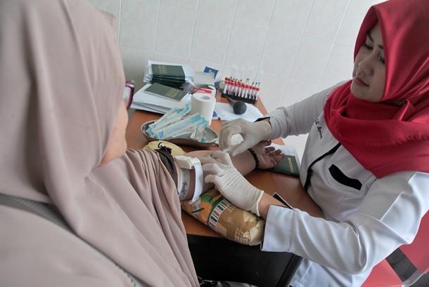 Petugas mengambil sampel darah calon jemaah haji di Puskesmas Dempo, Palembang, Sumsel, Selasa (5/7).
