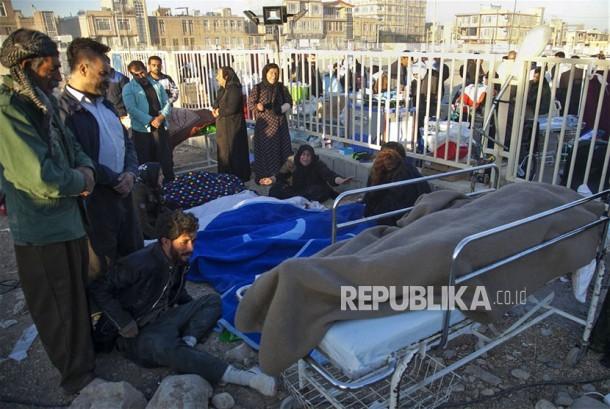 Warga mengevakuasi korban tewas gempa di kota Sarpol-e-Zahab di Provinsi Kermanshah, Iran, Senin (13/11).