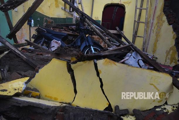 Warga membersihkan material reruntuhan bangunan rumah pasca gempa bumi di Desa Sumelap, Kota Tasikmalaya, Jawa Barat, Sabtu (16/12).
