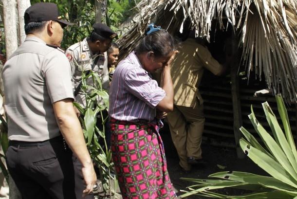 Adolfina Naonin (tengah) menangis ketika Bupati Kabupaten Kupang Ayu Titu Eki meninjau dirinya yang tinggal di kandang babi dengan seekor babi di desa Oebesi Kabupaten Kupang NTT Selasa (15/3).