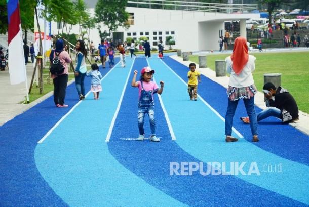 Anak-anak berlarian di Jogging track baru berlapis Karet empuk di Lapangan Gasibu, Kota Bandung, senin (19/9). Wajah baru Lapangan Gasibu, menjadi daya tarik tersendiri bagi masyarakat. (Republika/Edi Yusuf)