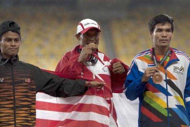 Atlet Indonesia Endi Nurdin Tine (tengah) menggigit medali emas yang diraihnya setelah menjuarai nomor lari 800 meter putra Asean Para Games XI Kuala Lumpur, di Stadion Bukit Jalil, Kuala Lumpur, Malaysia, Selasa (19/9).