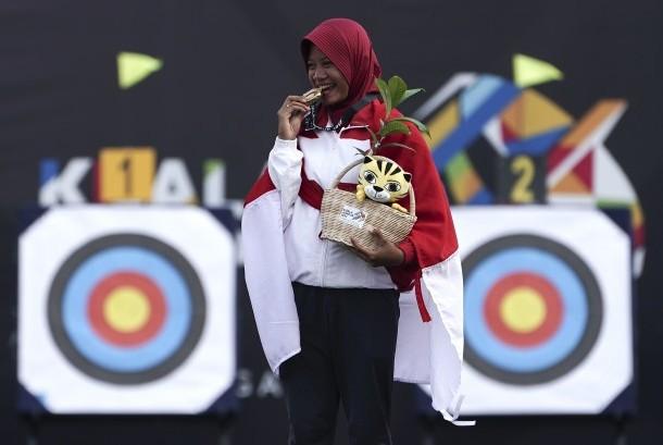 Atlet panahan Indonesia Diananda Choirunnisa menggigit medali emas ketika upacara penganugerahan medali panahan nomor recurve putri di Synthetic Turf Fild, Kawasan Bukit Jalil, Malaysia, Minggu (20/8).