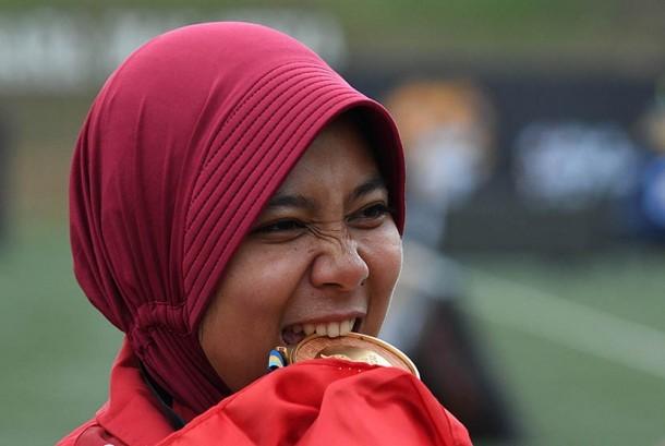 Atlet panahan putri Indonesia Sri Ranti menggigit medali emas setelah menjuarai final nomor compound putri SEA Games XXIX di Synthetic Turf Fild, kawasan Stadion Bukit Jalil, Kuala Lumpur, Malaysia, Rabu (16/8).