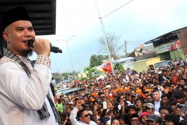 Bakal calon Wakil Bupati Bekasi yang juga musisi Ahmad Dhani (kiri) menghibur massa pendukungnya usai melakukan pendaftaran pencalonan Bupati dan Wakil Bupati Bekasi di Kabupaten Bekasi, Jawa Barat,