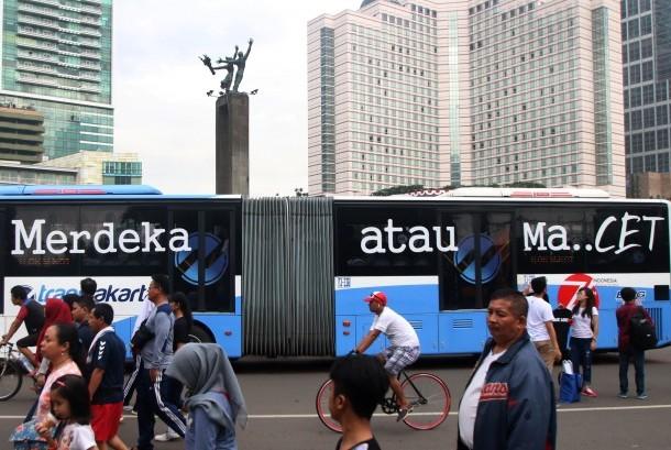Bis TransJakarta yang bertuliskan Merdeka Atau Macet melintasi area Car Free Day di kawasan Bundaran HI, Jakarta, Minggu (14/8).