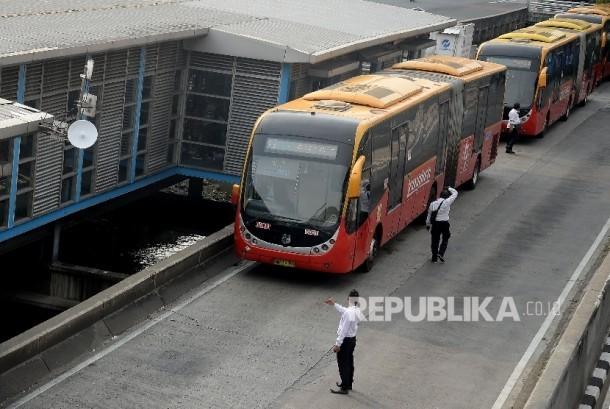 Bus Transjakarta menaikan dan menurunkan penumpang di Halte Harmoni, Jakarta, Senin(1/5).