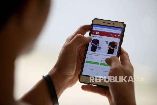 Calon pembeli melihat koleksi fashion terbaru mealui salah satu gerai E-Commerce melalui telfon genggamnya di Jakarta, Senin (31/7).