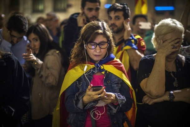 Demonstrators listen to the speech of Catalan leader Carles Puigdemont outside Palau Generalitat in Barcelona, Spain, Saturday (October 21).