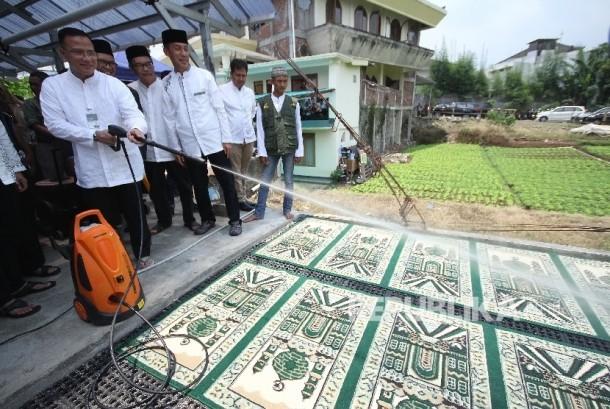 Direktur Distribution and Service Bank Syariah Mandiri (BSM) Edwin Dwidjajanto menyemprotkan air saat peresmian Program Cuci Karpet 1.000 Masjid Se-Bandung Raya bekerjasama dengan Bank Syariah Madiri (BSM) di Masjid Al Hidayah, Setiabudi Regency, Kabupaten Bandung Barat, Senin (23/10).