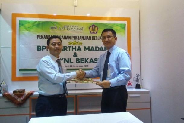 Direktur Utama BPRS Artha Madani Cahyo Kartiko (Kiri) berjabat tangan dengan Kepala Kantor KPKNL Partolo usai menandatangani kesepakatan kerja sama lelang di kantor pusat BPRS Artha Madani Kota Bekasi, Jawa Barat