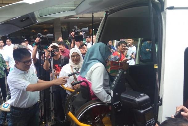 Direktur Utama BSM Toni Subari mendampingi pemudik penyandang disabilitas memasuki mobil akses di kantor pusat BSM, Jumat (23/6).