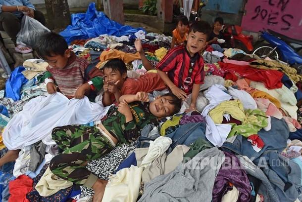 ejumlah anak korban banjir bandan sungai Cimanuk bermain di atas baju yang sumbangan di Cimacan, arogong, Kabupaten Garut, Jawa Barat, Jumat (23/9). Berbagai bantuan berupa makanan, pakaian dan kebutuhan untuk anak terus disalurkan ke posko darurat.