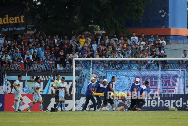 enjaga gawang Persela Lamongan Choirul Huda ditandu petugas kesehatan ketika bertanding melawan Semen Padang dalam lanjutan Gojek Traveloka Liga 1 di Stadion Surajaya Lamongan, Jawa Timur, Minggu (15/10).