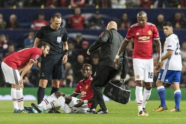 Gelandang Manchester United (MU), Paul Pogba terduduk karena cedera pada laga Liga Champions lawan FC Basel di Old Trafford pekan lalu. Pogba diperkirakan akan cedera panjang.